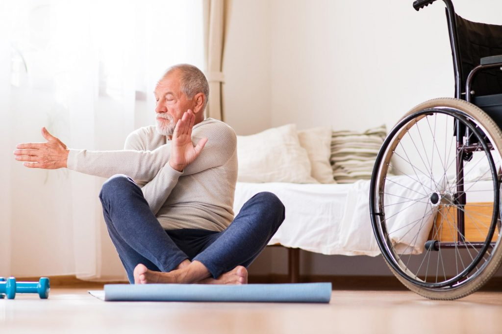 Man sat on mat on the floor stretching, with a wheelchair next to him