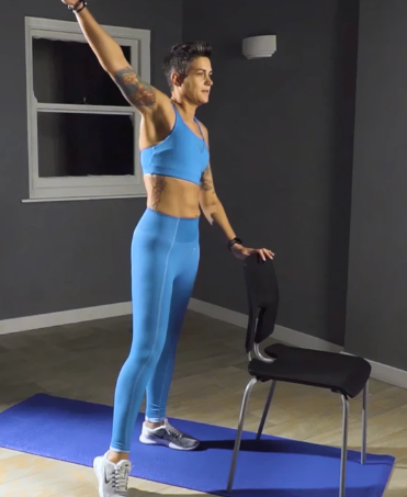 Woman standing in gym clothes with one arm on chair, stretching her other arm above