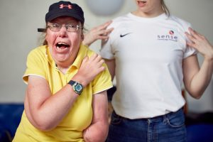 A Disabled woman is pictured stretching and smiling