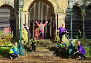 A group of seven young adults from DanceSyndrome show off their dance moves on some steps in front of a stone gated archway, funded by the Tackling Inequalities Fund