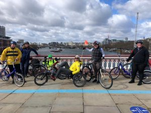 A group of Wheels for Wellbeing participants pose together on a bridge with a view of the river Thames in London