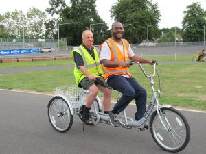 A Wheels for Wellbeing instructor and participant cycle together on an accessible tandem bicycle.