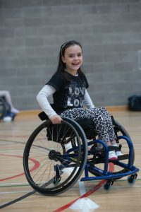 A girl smiles into the camera whilst sat in a wheelchair in a sports hall