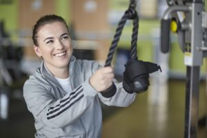 A young woman uses the cable machine at the gym