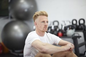 A young man looks at the camera whilst sat in the gym