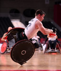A wheelchair basketball player for Team GB topples towards the court