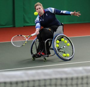Louise Hunt is pictured at the baseline of the tennis court striking a ball