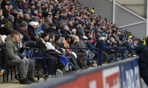 Disabled fans in wheelchairs watch from the stands of a football ground
