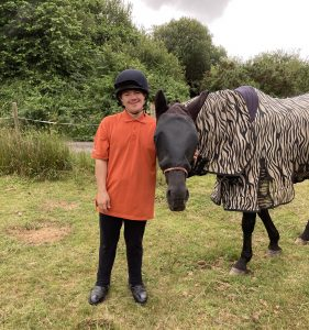 A young man, Rory is pictured next to his favourite horse, which has a protective coat on. He looks happy and joyful