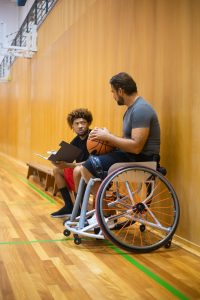 A coach sits next to and talks with a wheelchair basketball player
