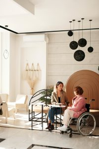 A woman in a wheelchair and a non-disabled woman sit together at a cafe table and are talking