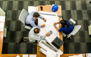 several people share a large desk to work together